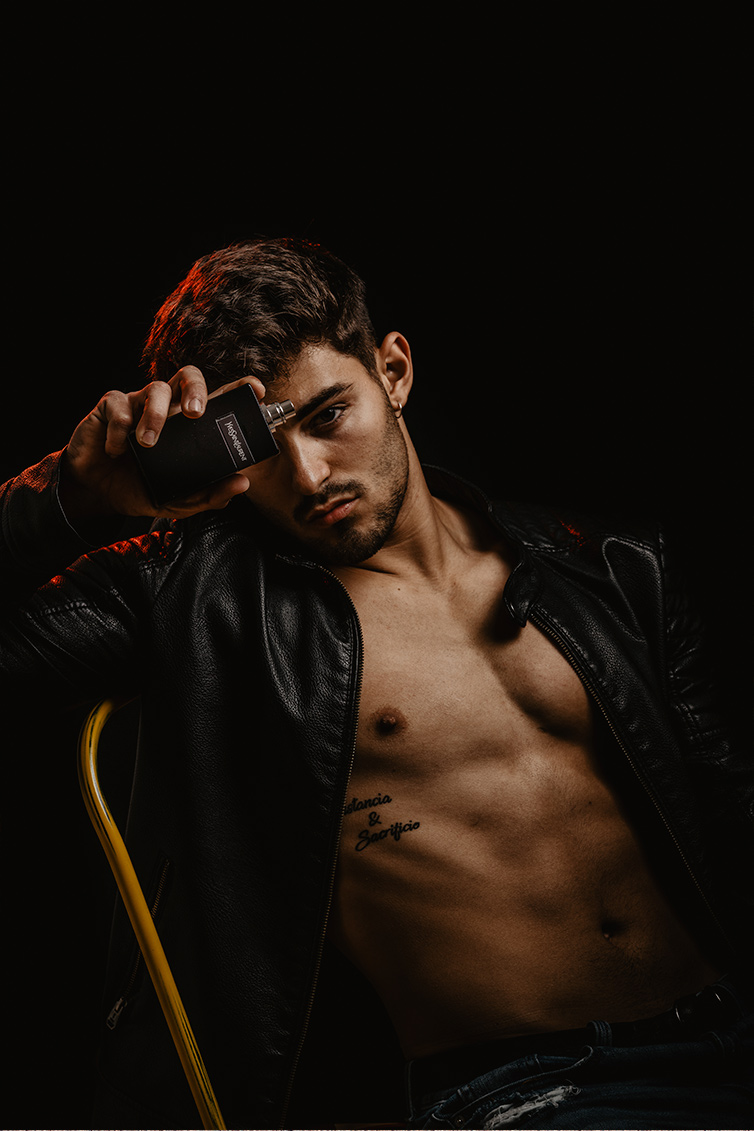 chico moreno fitness elegante con chaqueta de cuero y torso desnudo con perfume yves saint laurent trabajo influencer malephotography